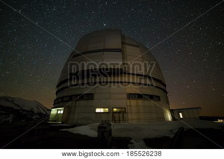 Night view. A special astrophysical observatory against the background of the starry sky and snowy peaks of the Arkhyz mountains.