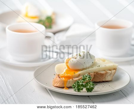 Delicious sandwich with poached egg and fresh cheese, hot tea in white cup