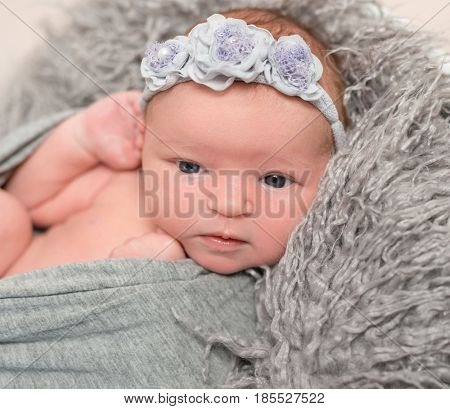 Adorable baby in gray wrap trying to crawl out of it, flowery hairband, furry pillow