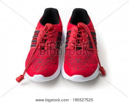 Bright red running shoes with black stripes on side, long shoelaces isolated on white background