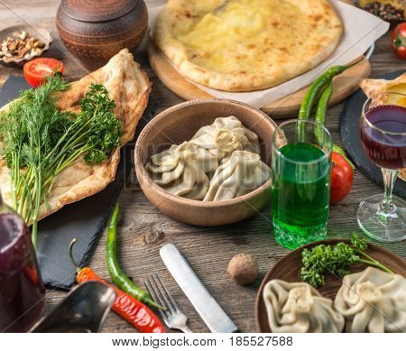 Spicy tatar cuisine, khinkali, khachapuri, laying on the table with cheese and pepper, topview