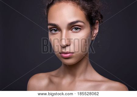 Closeup portrait of Beautiful brunette woman with clean skin without makeup. Beauty portrait on dark background.