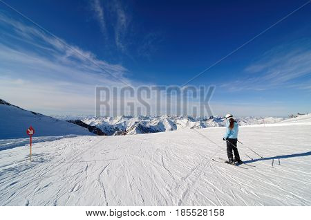 Skier on piste in Hintertux Zillertal Austria with clouds and blue sky
