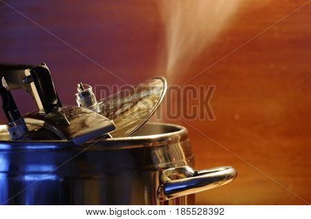 Steam escaping from lid of pressure cooker with reflection of modern kitchen. Indian style cooking rice or dhal
