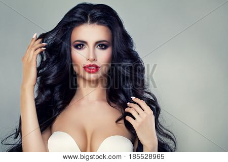 Fashion Portrait of Beautiful Brunette Woman with Long Curly Hair and Perfect Makeup