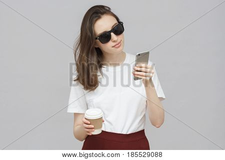 Portrait Of Beautiful European Hipster Girl Isolated On Grey Background Wearing Black Sunglasses Wit