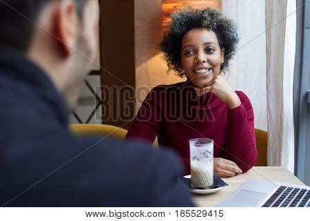Indoor Photo Of Young Beautiful African American Lady Captured Behind Her Boyfriend's Back Sitting A