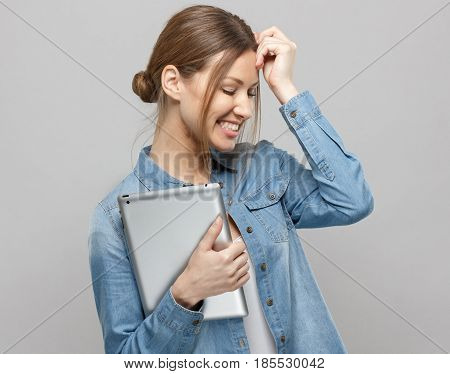Horizontal Photo Of Shy Attractive Lady Isolated On Grey Background Smiling Positively And Holding T