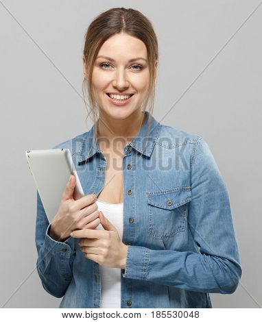 Vertical Closeup Of Beautiful Female Standing Isolated In Grey Background Holding Tablet Device With