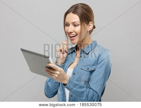 Portrait Of Attractive European Female, Holding Tablet, While Posing Against Grey Background.