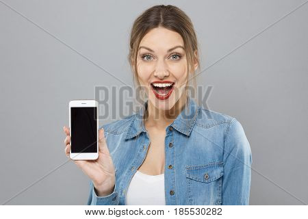Indoor Shot Of Stylish Beautiful Young Female Isolated On Gray Background Presenting Blank Cellphone