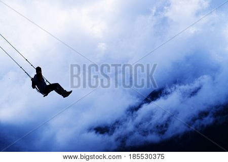 A silhouette of man swinging through the clouds on a swing