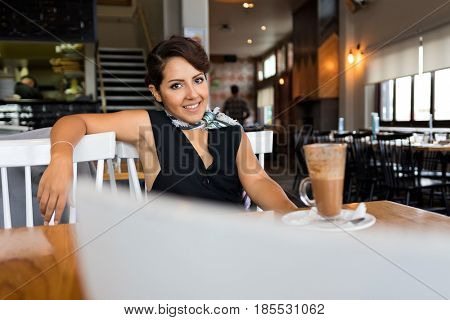 Smiling young woman drinking coffee in cafe