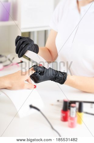 The manicure master shapes the nails with a nail file. Hand care in the salon.