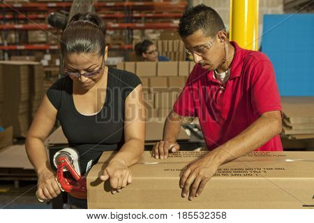 Hispanic workers taping box in warehouse