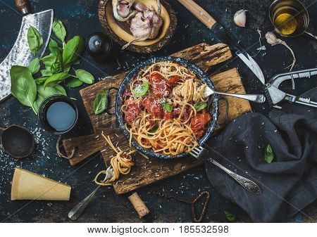 Italian style pasta dinner. Spaghetti with tomato and basil in plate on wooden board and ingredients for cooking pasta over dark blue plywood background, top view