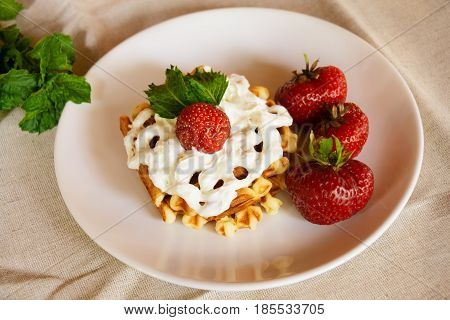 Waffles with whipped cream and strawberries. Selective focus