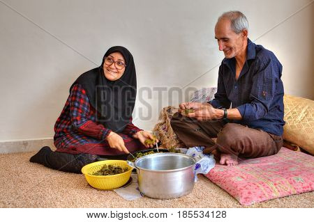 Bandar Abbas Hormozgan Province Iran - 15 april 2017: An elderly Iranian couple is preparing a dish of Iranian cuisine dolmeh sitting on the carpet at home.