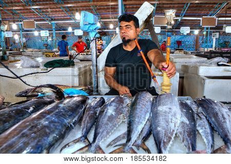 Bandar Abbas Hormozgan Province Iran - 15 april 2017: Fresh tuna lies on the ice in the fish market one adult man seller smokes a hookah.