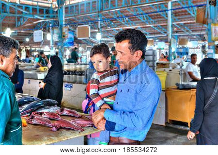 Bandar Abbas Hormozgan Province Iran - 16 april 2017: The fish market the tuna seller is talking to the buyer who is holding the little boy in his arms.