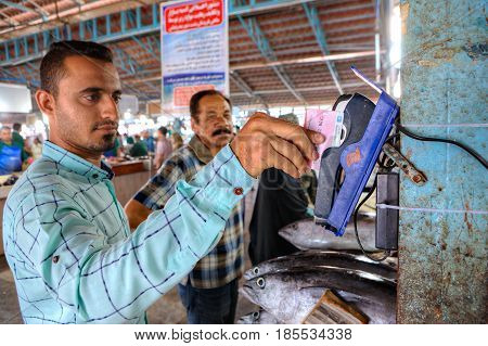 Bandar Abbas Hormozgan Province Iran - 16 april 2017: Persian man uses mobile terminal for payment by credit card in fish market.