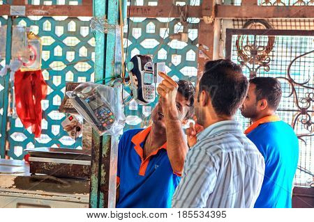 Bandar Abbas Hormozgan Province Iran - 16 april 2017: A Persian man pays a credit card for a purchase on the fish market using a mobile terminal.