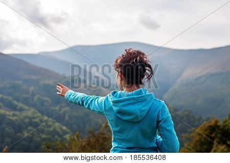 Young woman stands on a mountaintop. The concept of travel and lifestyle.