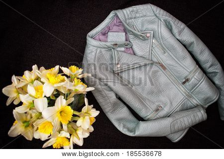 Gray Leather Jacket And A Bouquet Of Daffodils. Black Background. Fashionable Concept, Top View