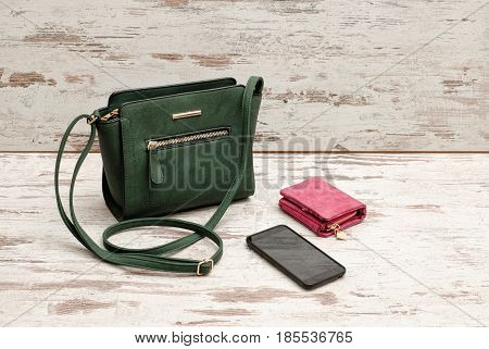 Small Green Female Bag, Pink Purse And Phone On A Wooden Background. Fashionable Concept
