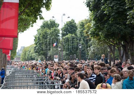 Paris France - July 14 2012. Townspeople and guests of Paris during the annual military parade in honor of the Bastille Day.