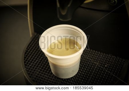 Black espresso coffee pouring down from brewing machine into plastic cup in studio shot
