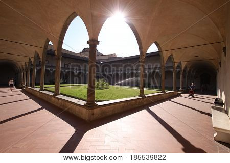 The sun shines through an archway in the courtyard of an old monastery