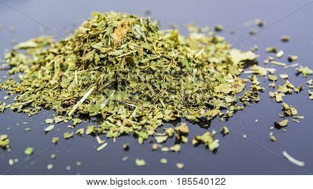 Dry herbs and flowers for herbal infusion forming a heap on neutral background, studio shot