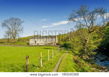 An isolated barn set in green English countyside.