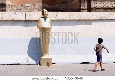 A boy turns to look at a street performer
