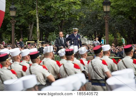 Paris. France. July 14 2012. French President Francois Hollande welcomes servicemen and citizens from the car during the parade on the Champs Elysees in Paris.