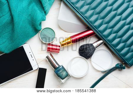 Woman's bag and it's content - lipstick, mascara, nail polish, smartphone, wet napkins, perfume in travel applicator, eye shadow, scarf