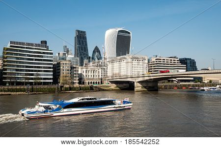 LONDON UK - 6 APRIL 2017: A view of an MBNA Thames Clipper river bus on the River Thames with London Bridge and the financial skyscrapers of the City of London in the background.