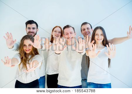 Happy group of friends standing together with hands up