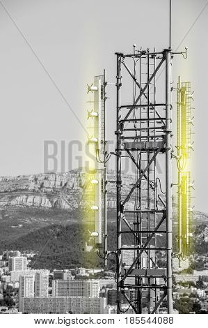 Aerial view of telecommunication tower with multiple antennas and data transmitters with light radio waves emission and with beautiful city in the background and wide mountain area