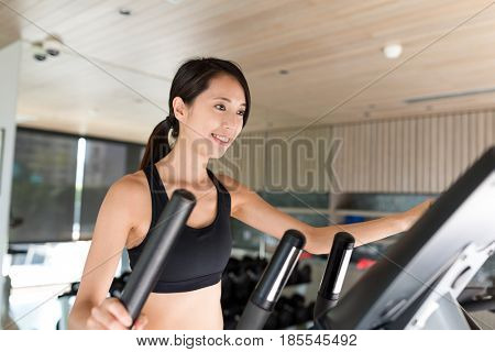 Woman training on Elliptical machine in gym