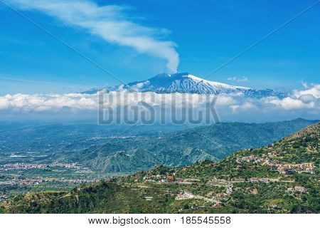 Smoking Mount Etna volcano, as seen from Taormina, Sicily