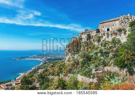 Hilltop church of holy madonna (sanctuario della madonna rocca) and bay of Giardini Naxos as seen from Taormina, Sicily, Italy