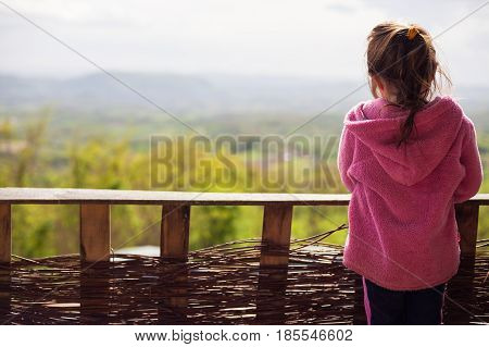 Young Girl In Front Of Fence