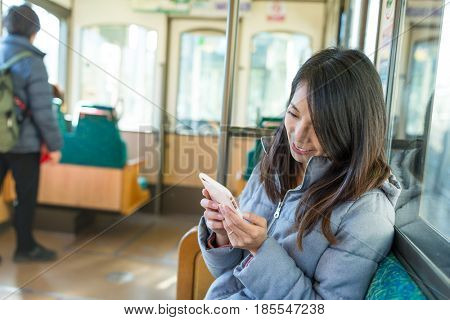 Woman using cellphone on train compartment