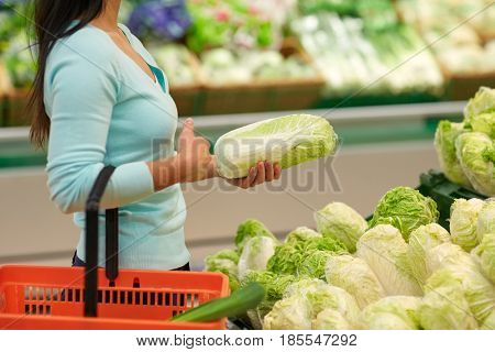 sale, shopping, food, consumerism and people concept - woman with basket buying chinese cabbage at grocery store