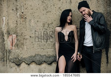Pretty fashion woman or girl with long brunette hair in sexy black dress and bearded man in stylish jacket and hat smoking cigarette with wine bottle on grungy cement wall. Bad habits copy space