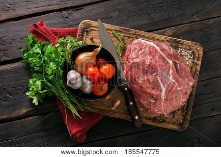 Fresh beef tenderloin with vegetables on a kitchen board on a dark wooden table top view