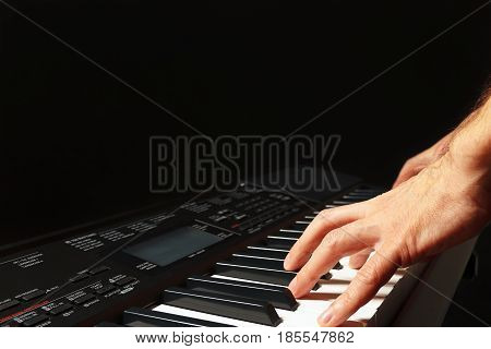 Hands of musician playing the synthesizer on a black background