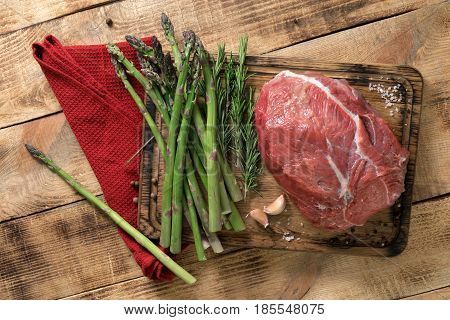 Fresh raw beef tenderloin with rosemary and asparagus on a wooden table top view. Ingredients for cooking healthy food